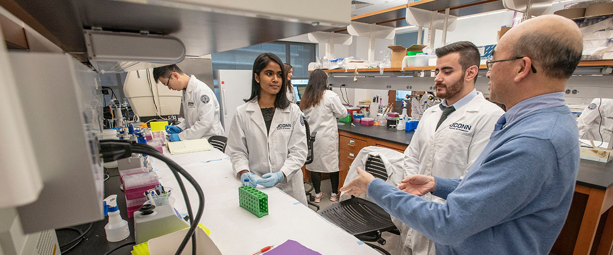 UConn Pharmacy students work with a professor inside a teaching laboratory