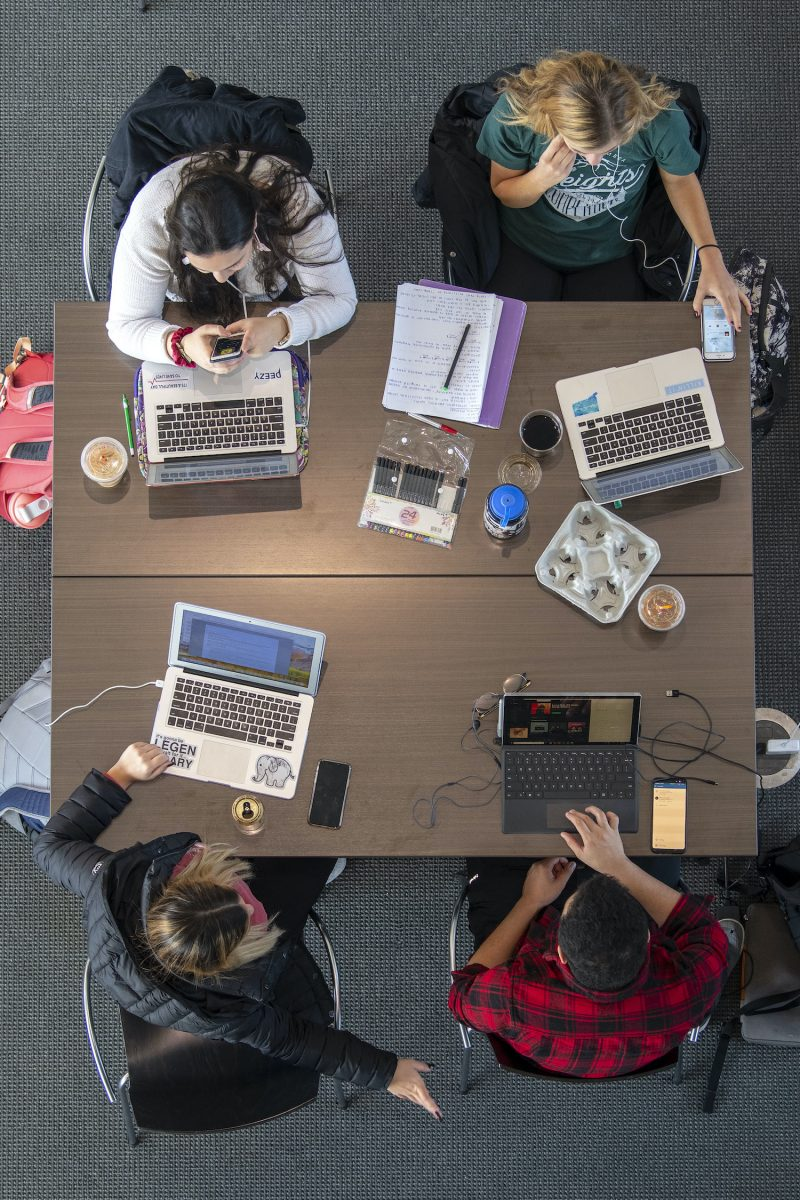 Four students studying around a table with laptop computers open.
